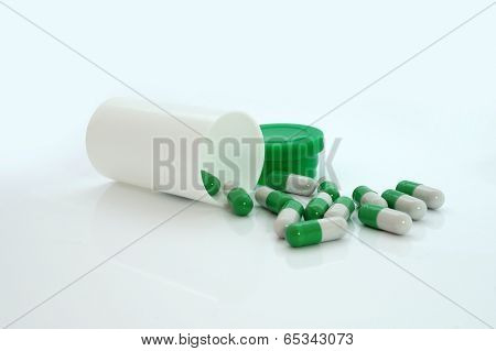 Green pills an pill bottle on white background