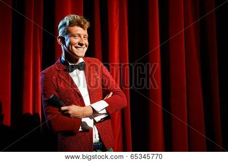 Portrait Of Anchorman At Show Against Red Curtain