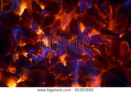 Hot glowing ember in a fireplace with beautiful blue flames