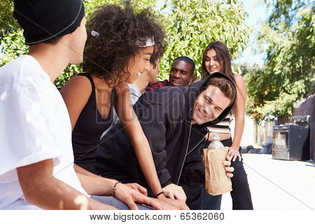 Gang Of Young People In Urban Setting Drinking Alcohol