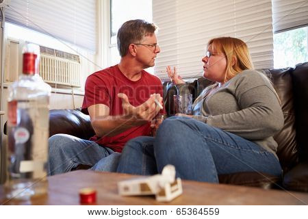 Couple Arguing On Sofa With Bottle Of Vodka And Cigarettes