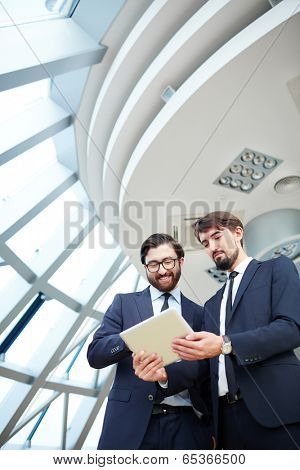 Image of young businessman holding touchpad while listening to explanation of his colleague at meeting