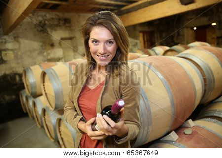 Smiling woman holding bottle of wine in cellar