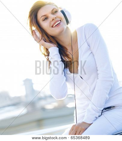 Pleasant young girl touches her headphones