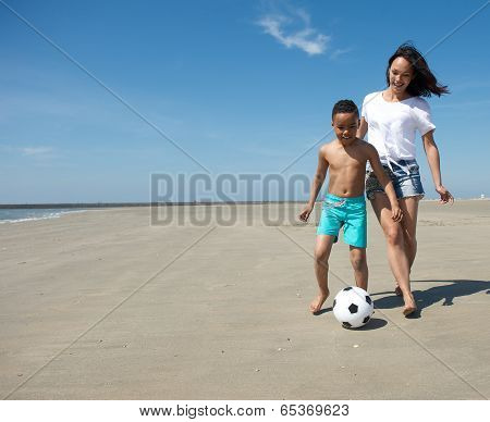 Mother Playing With Ball Together With Son