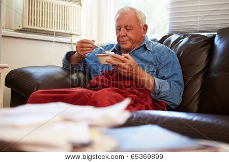Senior Man With Poor Diet Keeping Warm Under Blanket