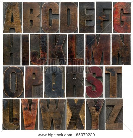 a complete English uppercase alphabet - a collage of 26 isolated antique wood letterpress printing blocks, stained by dark color inks