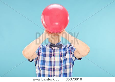 Man blowing up a balloon on blue background