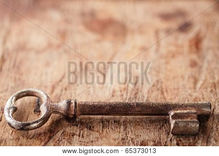 large and small rusty vintage metal keys on old wooden background, shallow dof