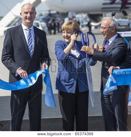 BERLIN, GERMANY - MAY 20, 2014: German Chancellor Angela Merkel (C), Turkish Minister of transport Lutfi Elvan (R) open up the International aviation and space exhibition ILA.