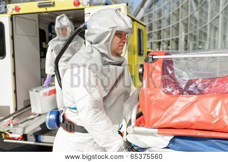 Biohazard medical team member with stretcher outdoors by ambulance