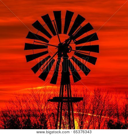 Antique Windmill Silhouetted By A Colorful Orange Sky.
