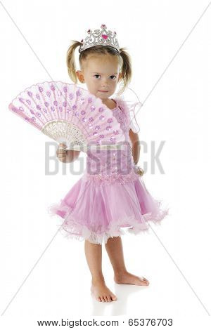 A beautiful preschooler dressed as a princes in pink, shyly holding an opened sparkly-pink fan.  On a white background.