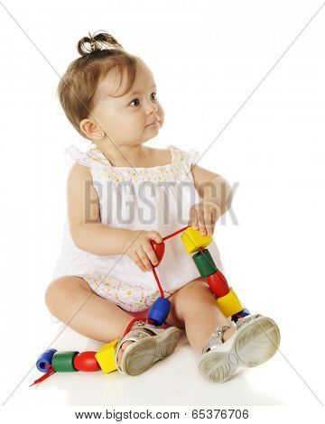 A beautiful baby girl looking off to the side as she's moving giant wooden beads along a string.  On a white background.