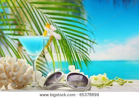 Blue curacao cocktail,sunglasses and seashells on beach table.