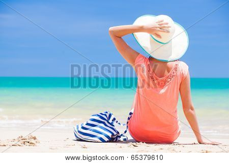 back view of a woman with stripy bag and straw hat lying on beach