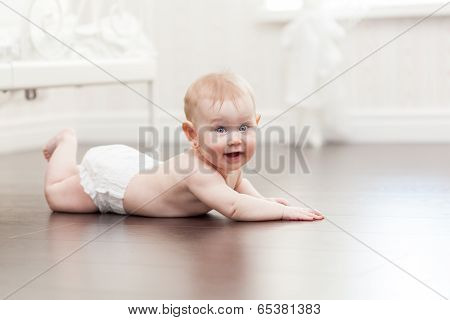 Happy Seven Month Old Baby Girl Crawling On A Hardwood Floor