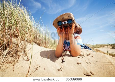Little boy searching with binoculars at the beach dressed as explorer concept for nature, discovery, exploring and education