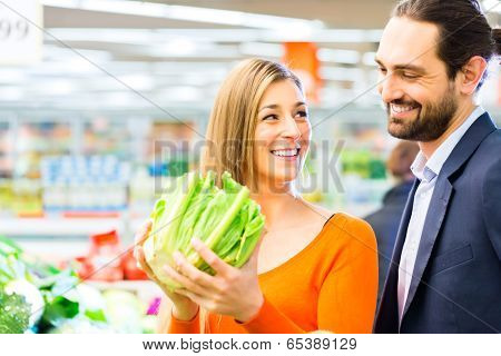Couple selecting vegetables while grocery shopping in supermarket