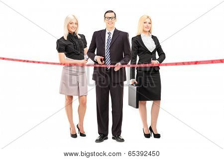 Full length portrait of a business team cutting a red tape isolated on white background