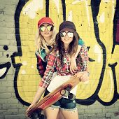 foto of skate board  - Two teen girl friends having fun together with skate board - JPG