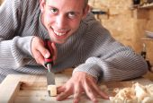 stock photo of gad  - Young carpenter with gad working and smiling - JPG