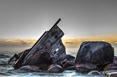 pic of shipwreck  - Wooden shipwreck beached on the rocky shore - JPG