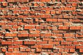 pic of mortar-joint  - This rugged red brick wall exhibits extruded mortar and an irregular surface - JPG