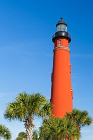 picture of inlet  - Flanked here by palms the brilliant red lighthouse at Florida - JPG