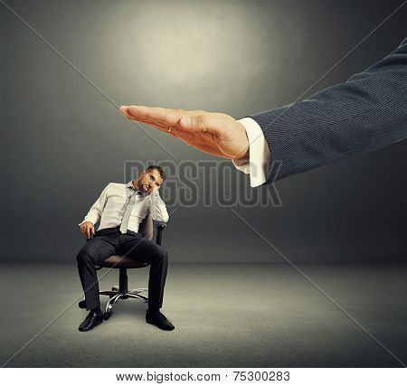 big hand ready to hit lazy businessman on the office chair. photo over dark background