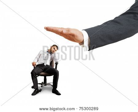 big hand ready to slap lazy businessman on the chair. photo over white background