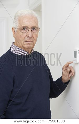 Worried Senior Man Turning Down Central Heating Thermostat