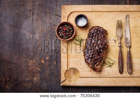 Grilled New York Striploin Steak With Salt And Pepper On Meat Cutting Board On Dark Wooden Backgroun