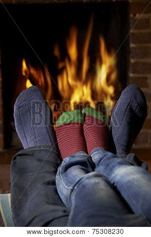 Father And Child Wearing Socks Warming Feet By Fire