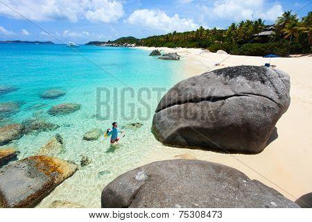 Above aerial view of young woman with snorkeling equipment at tropical beach among granite boulders at Virgin Gorda, British Virgin Islands, Caribbean