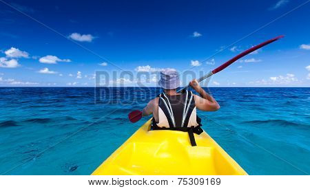 Caucasian man is kayaking in sea at Maldives