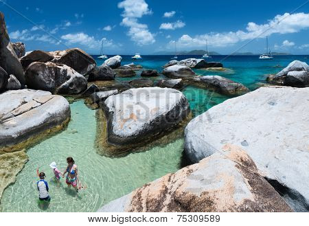 Family of mother and kids at The Baths beach area major tourist attraction at Virgin Gorda, British Virgin Islands, Caribbean