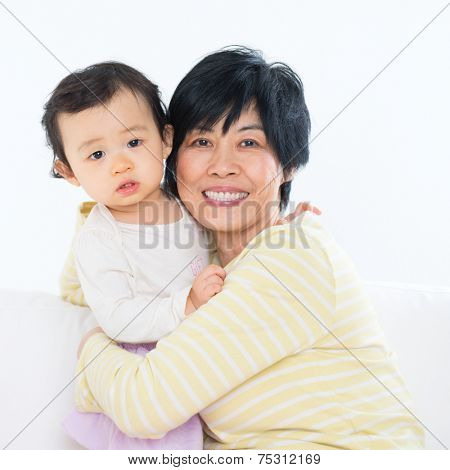 Asian family portrait, grandma and grandchild indoor living lifestyle at home.