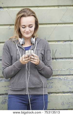 Teenage Girl Wearing Headphones And Listening To Music In Urban Setting
