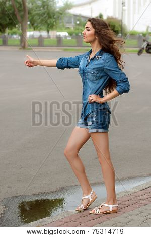 Side View Of A Woman Hitchhiking On City Road