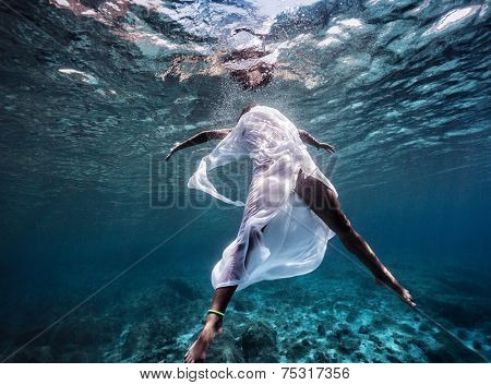 Fashionable model wearing white long dress dive into the water, dancing underwater, summer vacation, sport and art concept