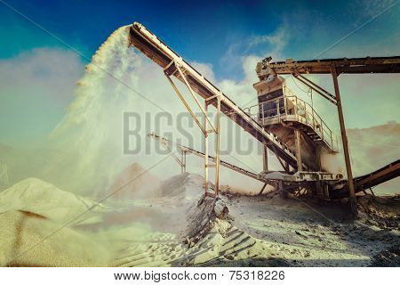 Vintage retro effect filtered hipster style image of Industrial background - crusher (rock stone crushing machine) at open pit mining and processing plant for crushed stone, sand and gravel