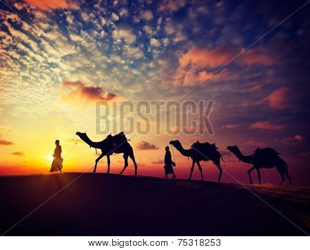 Vintage retro effect filtered hipster style image of  Rajasthan travel background - two indian cameleers (camel drivers) with camels silhouettes in dunes of Thar desert on sunset. Rajasthan, India