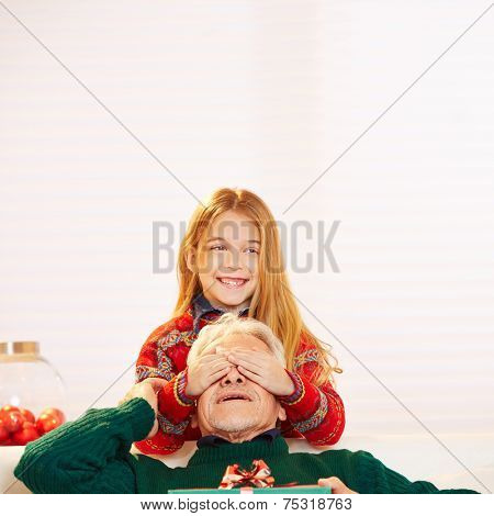 Happy girl holding eyes of her grandfather closed at christmas