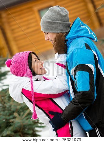 Half-length portrait of hugging couple looking at each other who wears warm caps and jackets during winter holidays