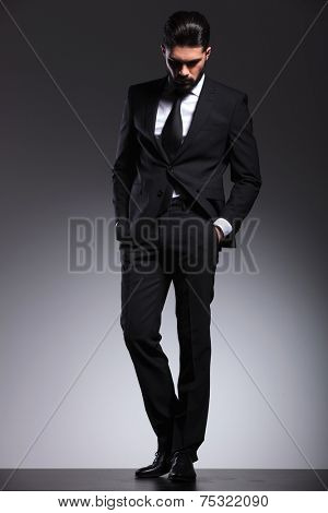 Full body image of a young elegant business man looking down while holding his hands in pockets.