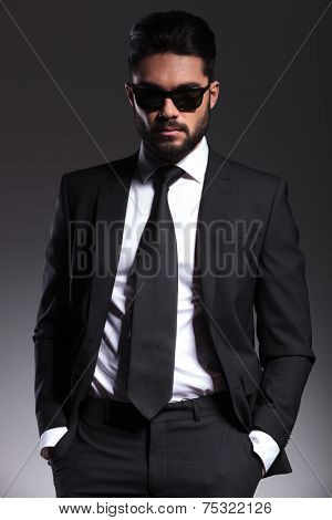 Portrait of a young elegant business man posing for the camera with his hands in pockets.