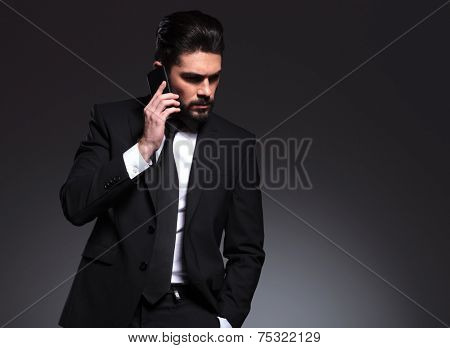 Elegant business man talking on the phone with one hand in his pocket, looking down