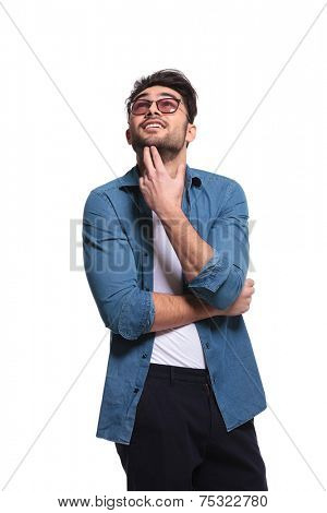 Young handsome man looking up while thinking, holding his fingers to his chin. Isolated