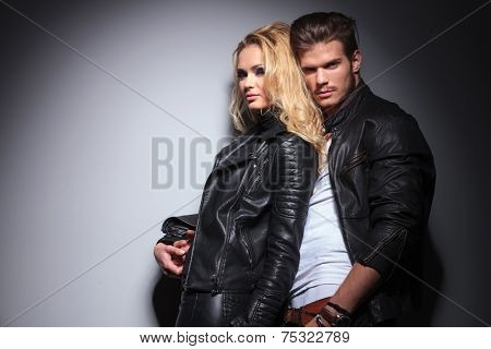 Attrative young fashion man holding his girlfriend while leaning on a grey wall, both looking at the camera.